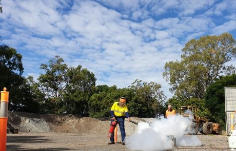 Construction working using a fire extinguisher | Astra Group Services