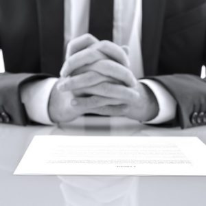 Guy siting in front of a contract | Astra Group