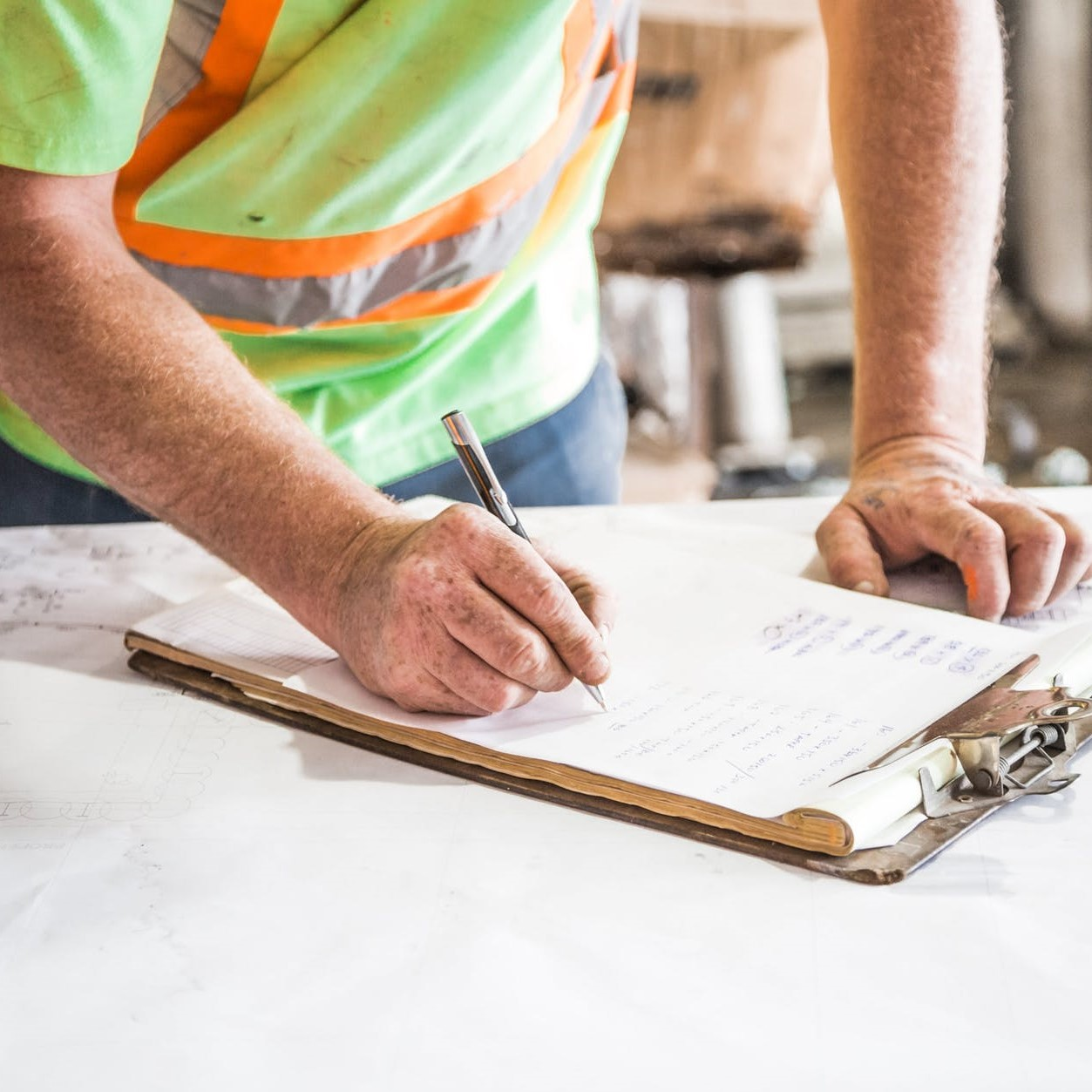 Builder checking his workers list | Astra Group Services