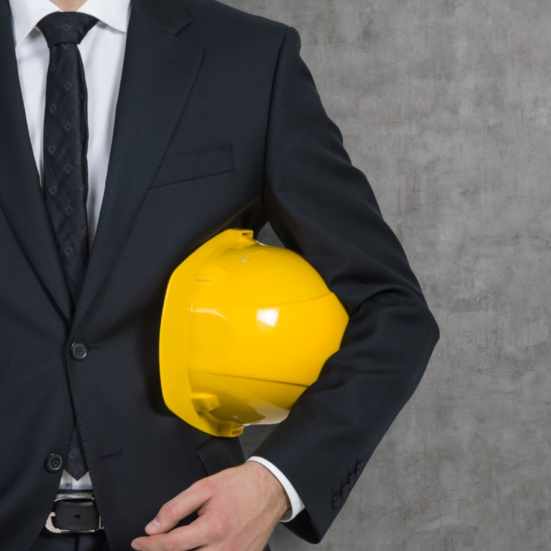 Guy dressed up in a suit holding a helmet | Astra Group Services