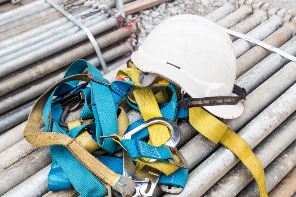 Safety helmet and safety harness at a construction | Astra Group Services
